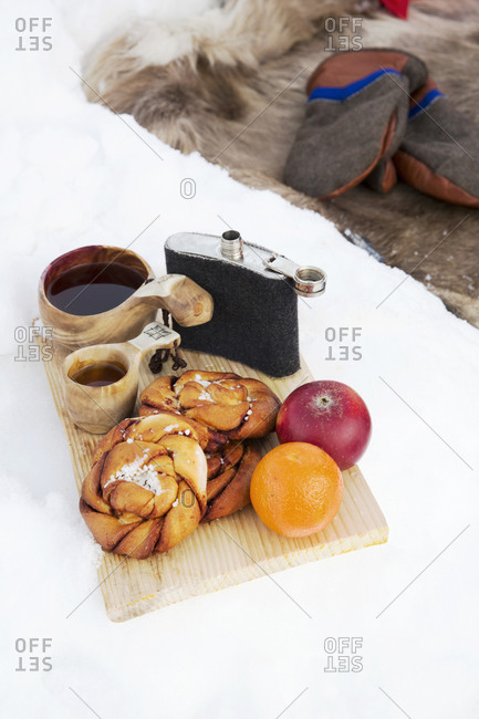 Hip flask and fruit on cutting board in winter