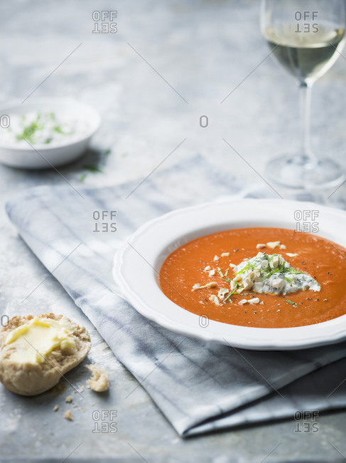 Soup on table with bread roll and wine