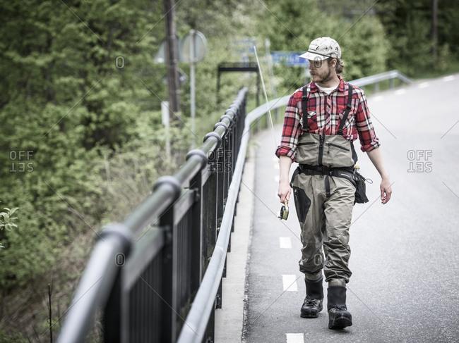 Fisherman walking on bridge