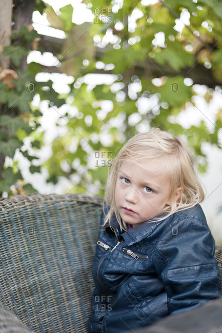 Portrait of boy sitting on chair outdoors