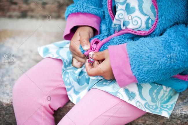 Girl sitting on steps, zipping sweatshirt