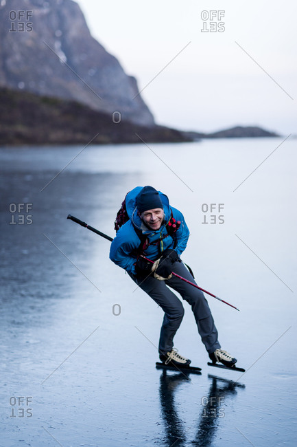 Portrait of man ice-skating on frozen lake