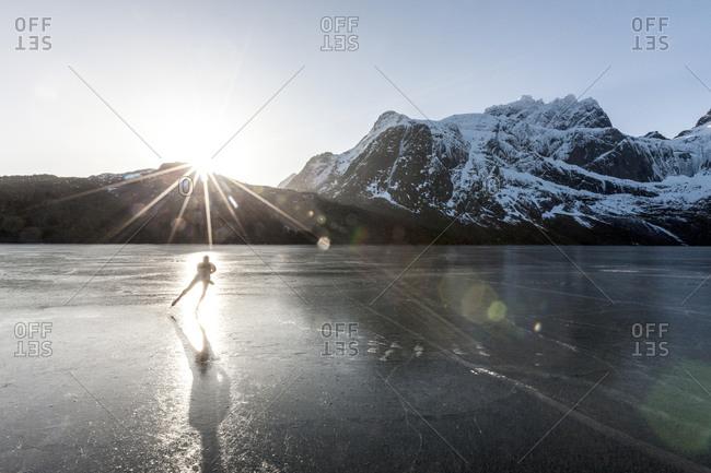 Man ice-skating on frozen lake at sunset
