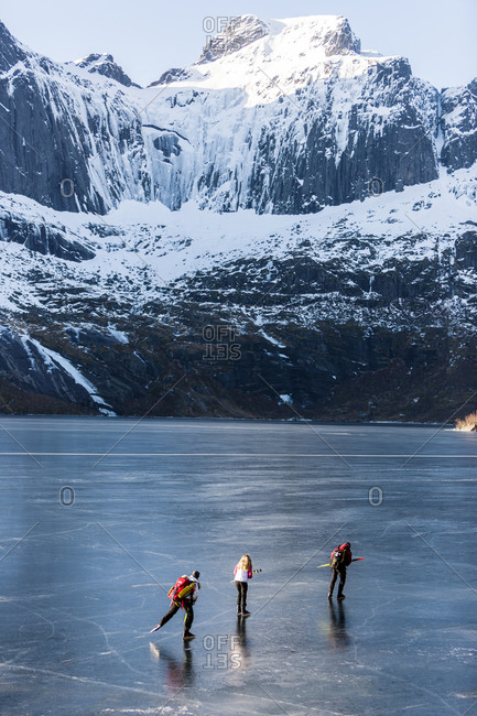 Friends ice-skating on frozen lake
