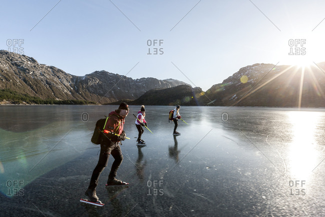 Friends ice-skating on frozen lake at sunset