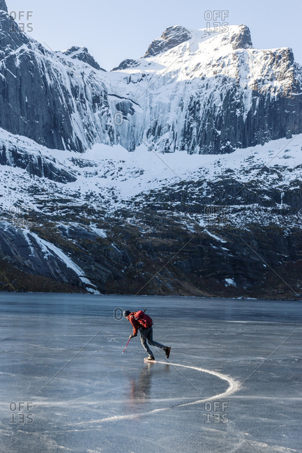Man ice-skating on frozen lake