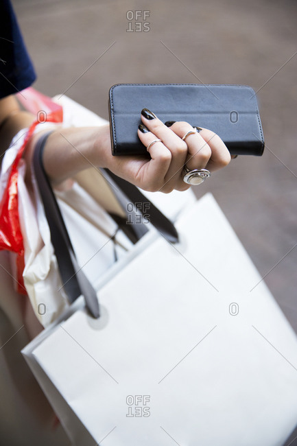 Close-up of woman with shopping bags and wallet