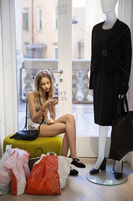 Young woman using cell phone in clothing shop
