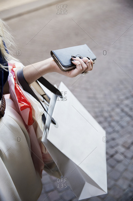 Close-up of woman with shopping bag and wallet