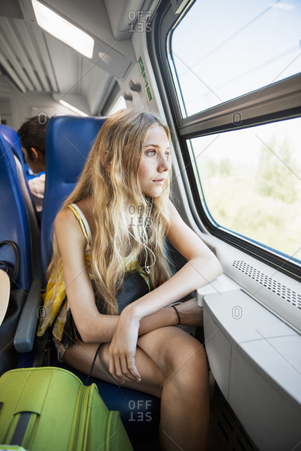 Young woman looking through window in train