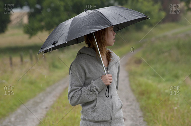 Young woman with umbrella in rain