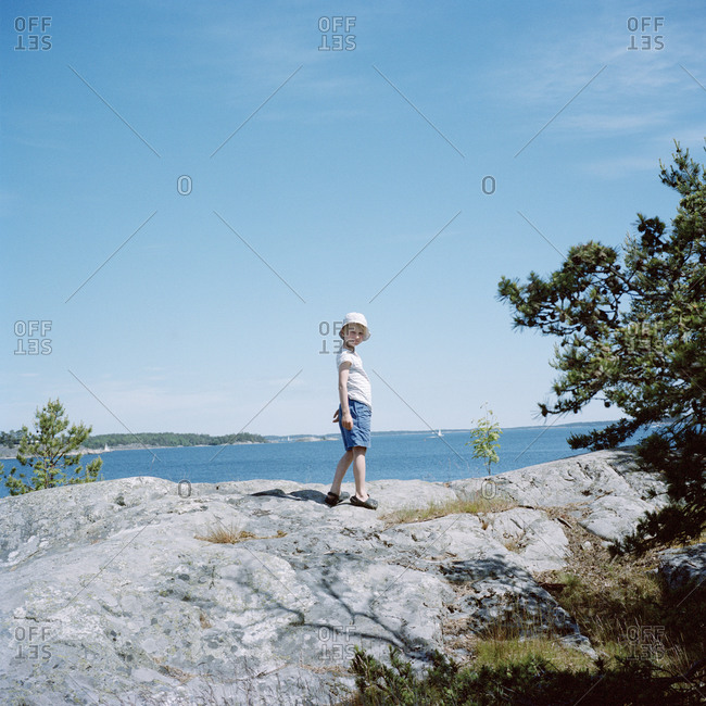 Portrait of girl standing on rock by lake