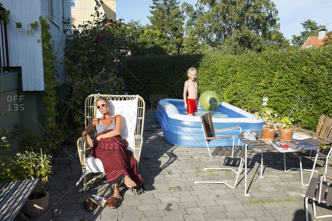 Mother sunbathing with son playing in swimming pool