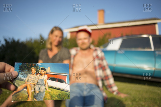 People sitting in front of house with person holding photo in foreground