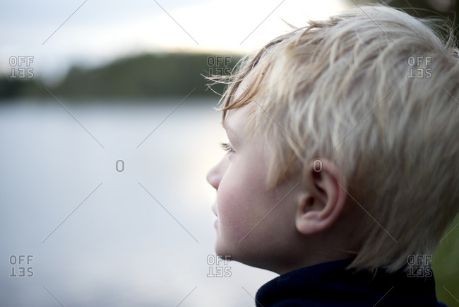 Blond boy looking at river