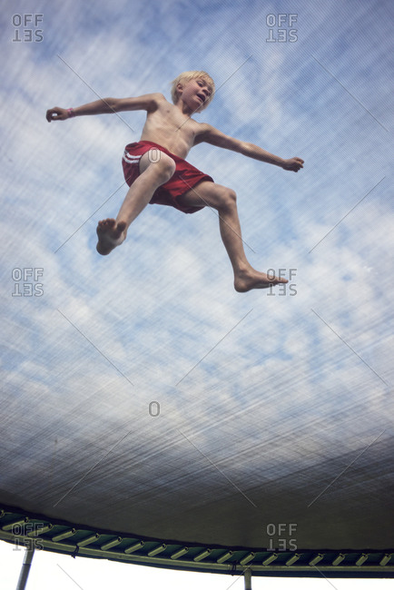 Low angle view of boy jumping on trampoline