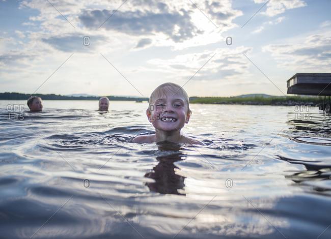 Three boys swimming in lake
