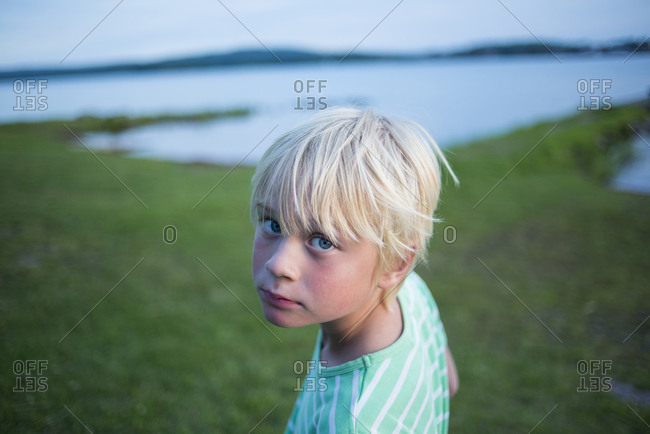 Portrait of blond boy standing next to river