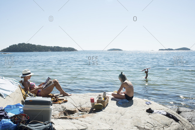 Mother sunbathing and children playing by sea