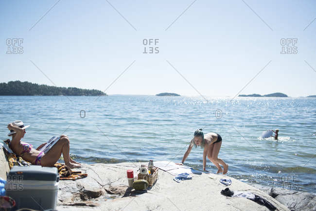 Women sunbathing by lake with boy playing in background
