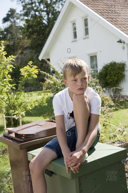Boy sitting on dustbin and looking away