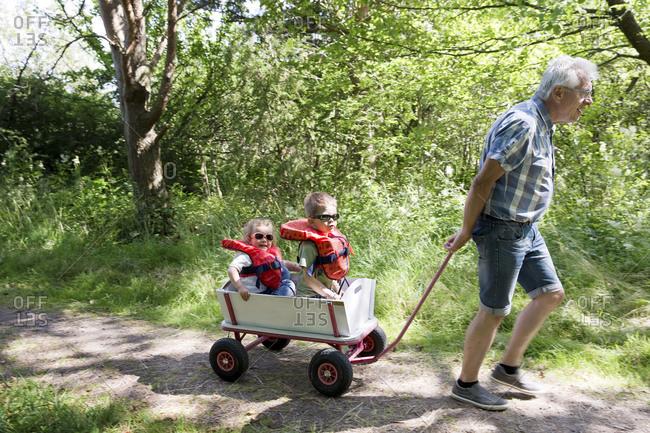 Grandfather pulling children in cart