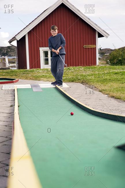 Boy playing minigolf