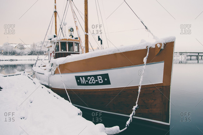 Snow-covered boat anchored in a harbor