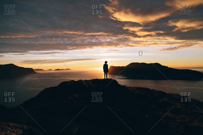 Silhouette of a person standing on a mountaintop at sunset in Norway