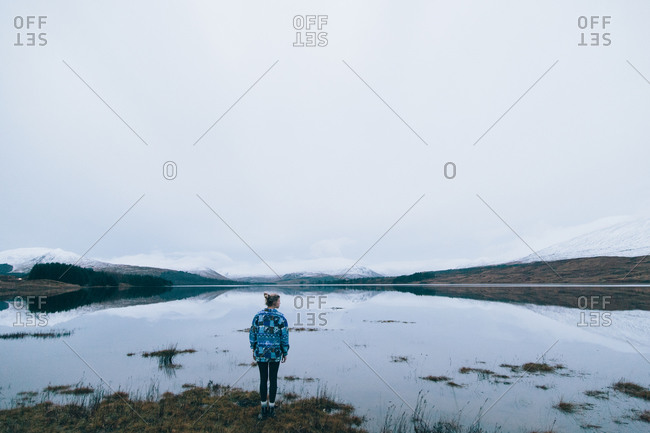Person standing on the edge of a loch in the UK