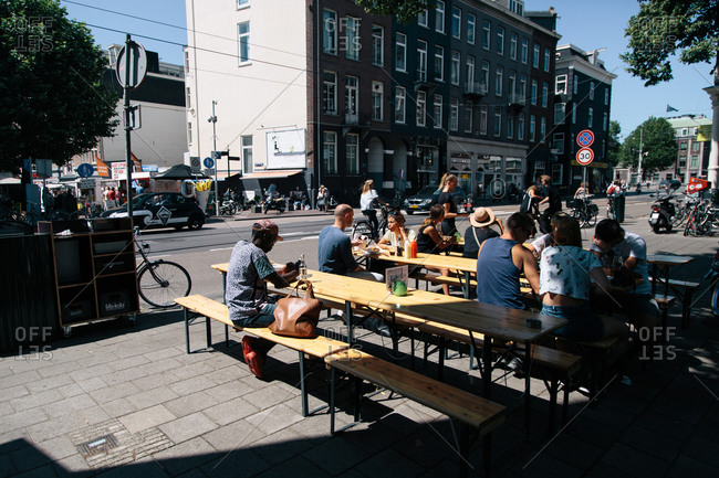 Amsterdam, Netherlands - July 21, 2015: People eating on benches at a sidewalk cafe in Amsterdam
