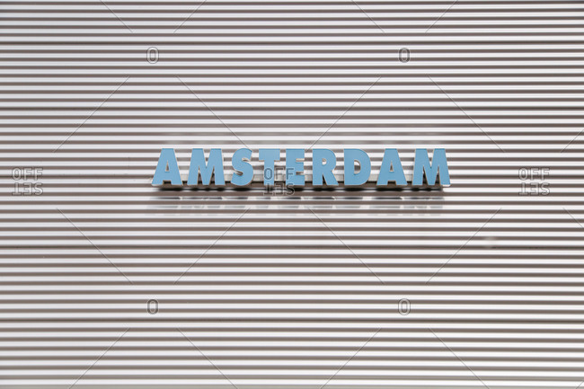 A sign reading 'Amsterdam' on the side of a corrugated metal wall