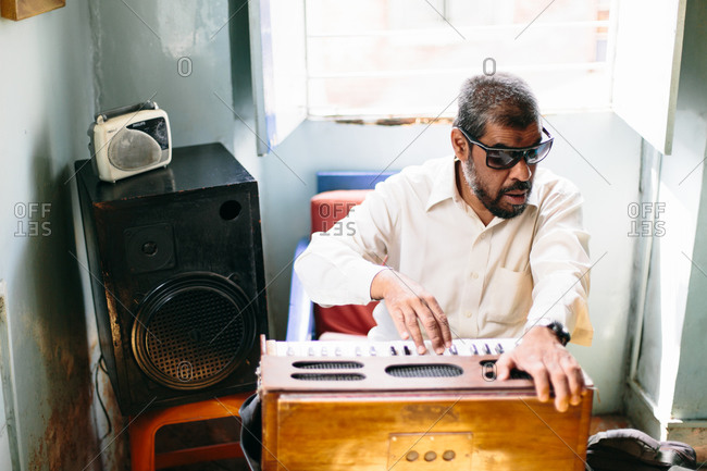 Man wearing sunglasses playing a small keyboard in a brightly lit room