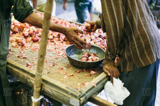 Man dropping onions into a bowl at a market in India