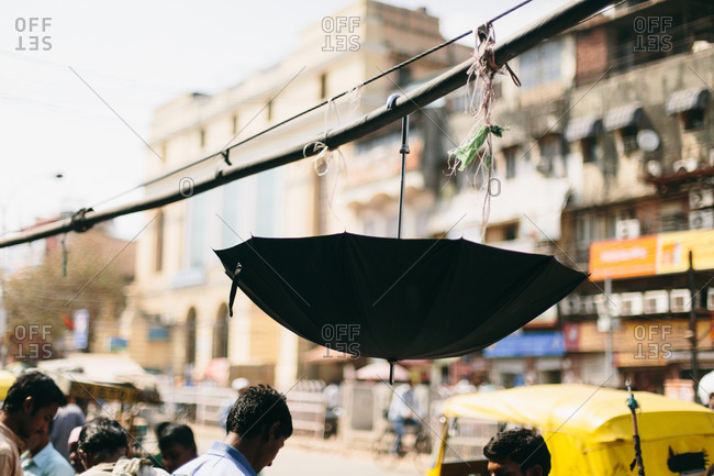 Umbrella hanging from a cable along a street in India