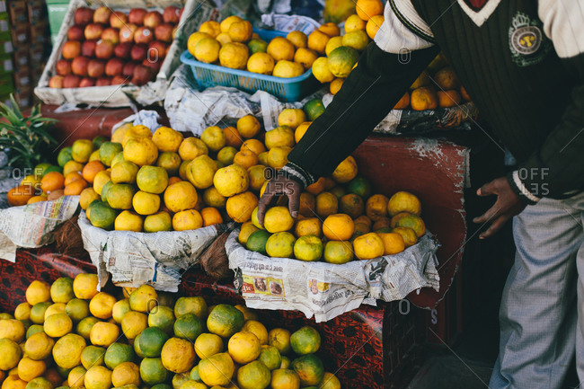 Man picking citrus fruit from a fruit stand in India