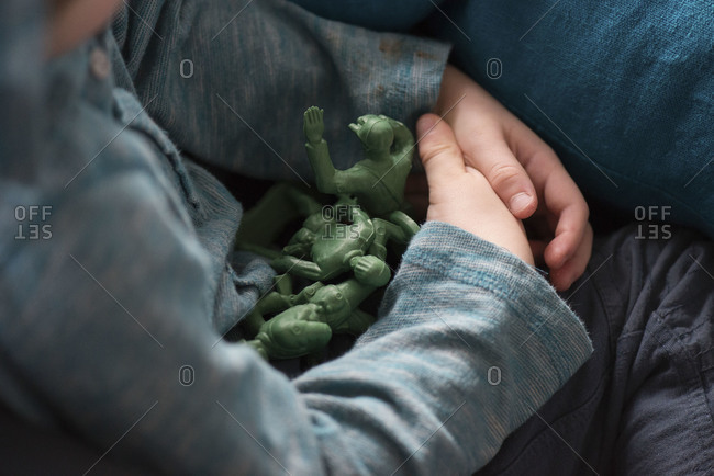 Boy cradling toy soldiers