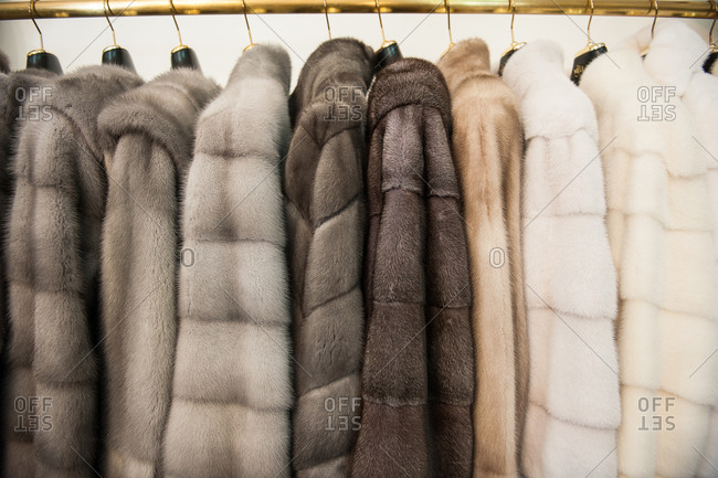 Fur coats hanging together on a coat rack
