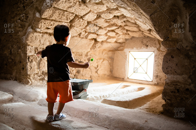 Young boy holding a lollipop standing inside the Fort of Bahrain