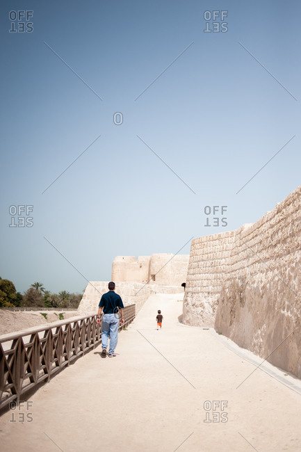 Father and son walking together along the ramparts of the Fort of Bahrain