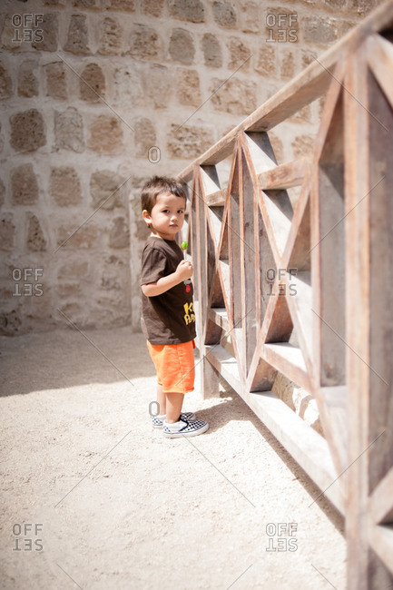 Young boy holding a lollipop standing outside the Fort of Bahrain