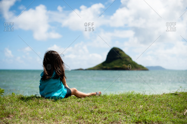 Girl sitting on a grassy shoreline overlooking the islet of MokoliI in Kaneohe Bay, Hawaii