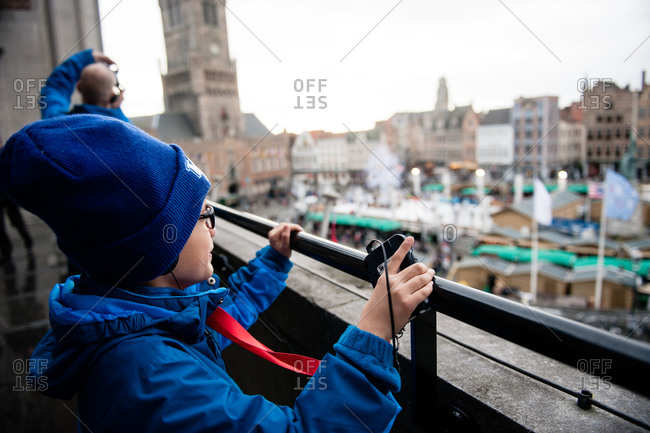 Bruges, Belgium - December 21, 2015: Boy looking out over the town square in Bruges, Belgium