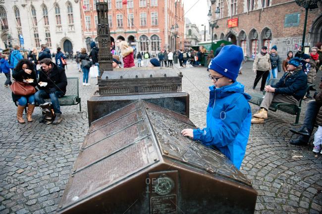 Bruges, Belgium - December 21, 2015: Boy looking at a kiosk in Burg Square in Bruges, Belgium
