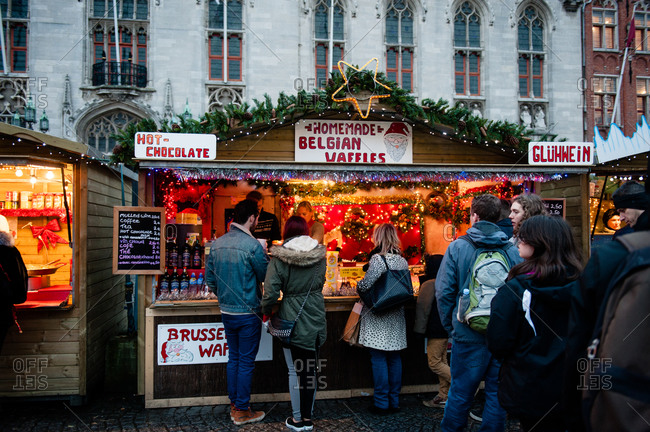 Bruges, Belgium - December 21, 2015: People lined up at a homemade Belgian waffle cart in a marketplace in Bruges, Belgium