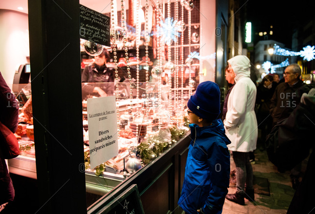 Brussels, Belgium - December 22, 2015: Boy looking through the window of a butcher shop