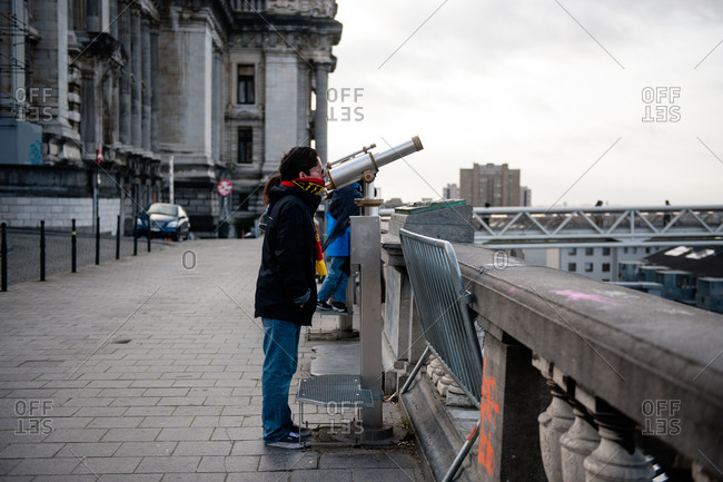 Brussels, Belgium - December 23, 2015: Teenage boy looking through telescope in Brussels, Belgium