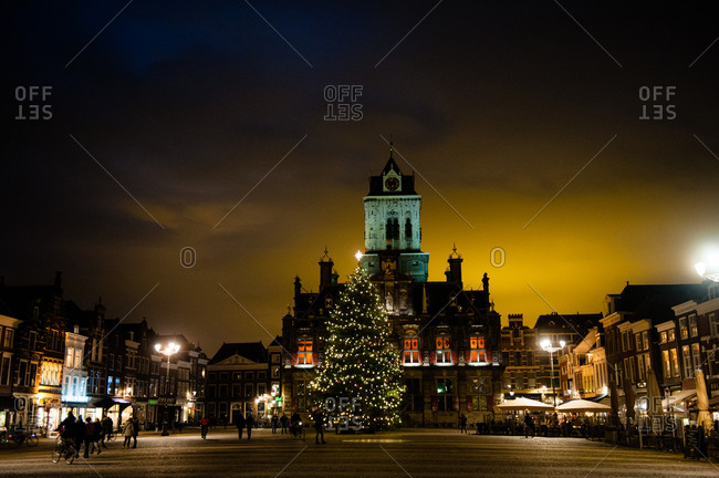 A Christmas tree at night in Market Square next to the Nieuwe Kerk Cathedral and Stadhius Townhall in Delft, Holland
