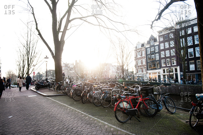 Bicycles parked on the street along a canal in Amsterdam