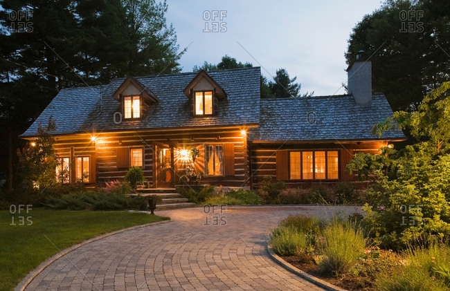 Reconstructed 1976 cottage style log home facade at dusk, Quebec, Canada